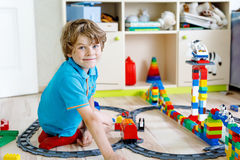 Little blond kid boy playing with colorful plastic blocks and creating train station Stock Images