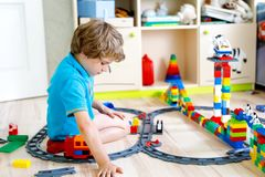 Little blond kid boy playing with colorful plastic blocks and creating train station. Adorable little blond kid boy playing with colorful plastic blocks and Stock Photography