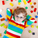 Little blond kid boy playing with lots of colorful plastic block Stock Photos