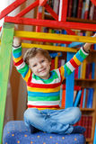 Little blond kid boy playing in selfmade wooden colorful house Royalty Free Stock Photos