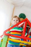 Little blond kid boy playing in selfmade wooden Royalty Free Stock Image