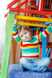 Little blond kid boy playing in selfmade wooden colorful house Stock Photo