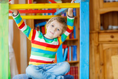 Little blond kid boy playing in selfmade wooden colorful house Stock Photography
