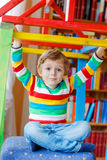 Little blond kid boy playing in selfmade wooden colorful house Stock Photos