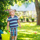Little blond kid boy playing with water can toy Stock Photography
