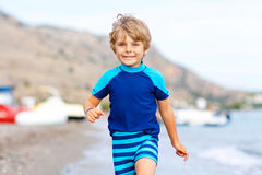 Little blond kid boy running ocean beach Stock Photo