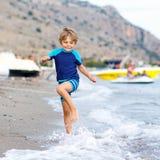 Little blond kid boy running ocean beach Royalty Free Stock Images