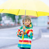 Little blond kid boy walking with big umbrella outdoors Stock Photo