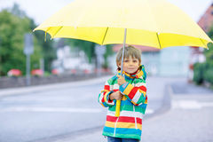 Little blond kid boy walking with big umbrella outdoors Royalty Free Stock Image