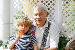 Little blond kid boy and young senior grandfather eating together ice cream in summer. Funny family outdoors Stock Photos