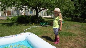 Blond kid fill pool from water hose at country house in summer. Gimbal motion stock video footage