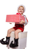 Little blond kid in red costume of dwarf holding big gift box with ribbon. Christmas concept Stock Photo