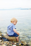 Little blond one year old boy sitting on a rock Royalty Free Stock Image