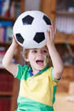 Little blond preschool boy of 4 years with football looking socc Stock Photo