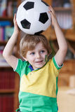 Little blond preschool boy of 4 years with football looking socc Stock Image