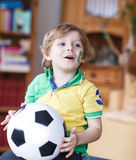 Little blond preschool boy of 4 years with football looking socc Royalty Free Stock Image