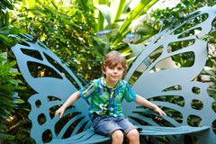 Little blond preschool kid boy discovering flowers and butterflies at botanic garden. Schoolchild interested in biology. Active educational leisure with kids royalty free stock image