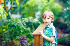 Little blond preschool kid boy discovering flowers, plants and butterflies at botanic garden. Schoolchild interested in. Biology. Active educational leisure stock photo