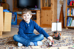 Little blond preschool kid boy playing with toy ship indoors Stock Photography