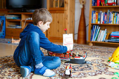 Little blond preschool kid boy playing with toy ship indoors Royalty Free Stock Photography