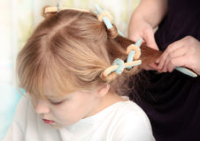 Little blond Russian girl with curlers on hair Stock Photos