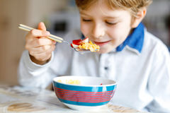 Little blond school kid boy eating cereals with milk and berries, fresh strawberry for breakfast Stock Images