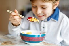 Little blond school kid boy eating cereals with milk and berries, fresh strawberry for breakfast Royalty Free Stock Photo