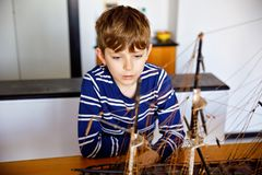 Little blond school kid boy playing with sailing ship model indoors. Excited child with yacht having fun after school at. Home. Happy boy building and creating royalty free stock photography