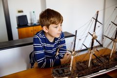 Little blond school kid boy playing with sailing ship model indoors. Excited child with yacht having fun after school at. Home. Happy boy building and creating royalty free stock photo