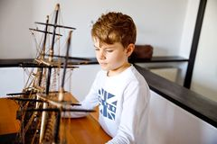 Little blond school kid boy playing with sailing ship model indoors. Excited child with yacht having fun after school at. Home. Happy boy building and creating stock photos