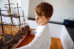 Little blond school kid boy playing with sailing ship model indoors. Excited child with yacht having fun after school at. Home. Happy boy building and creating stock image