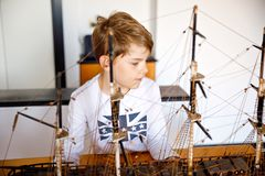 Little blond school kid boy playing with sailing ship model indoors. Excited child with yacht having fun after school at. Home. Happy boy building and creating stock photography
