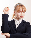 Little blond schoolgirl holds up the pen Royalty Free Stock Photo