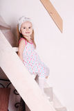 Little blond smiling girl in dress sitting on wooden stairs Royalty Free Stock Images