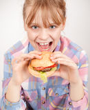 Little blond smiling girl eats hamburger Royalty Free Stock Image