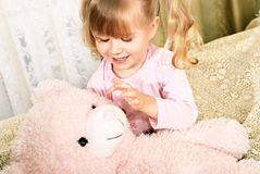 Little blond smiling girl with teddybear Royalty Free Stock Images