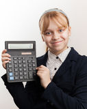 Little blond smiling schoolgirl with calculator Royalty Free Stock Photo