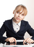 Little blond smiling schoolgirl with tablet device Royalty Free Stock Images