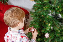 Little blond toddler boy decorating Christmas tree at home Stock Photo