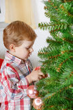 Little blond toddler boy decorating Christmas tree at home Royalty Free Stock Images
