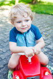 Little blond toddler boy driving red toy car Stock Photography