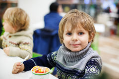 Little blond toddler boy eating ice cream iin shopping mall Stock Images