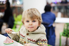 Little blond toddler boy eating ice cream iin shopping mall Royalty Free Stock Photos