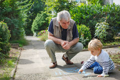 Little blond toddler boy and happy grandfather painting with cha Stock Photography