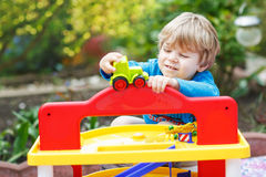 Little blond toddler boy playing with toy - car park station in Royalty Free Stock Photos