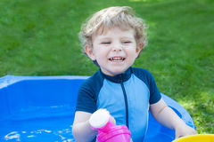 Little blond toddler boy playing with water in summer Stock Photo