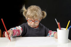 Little blond toddler girl making a drawing. Black background Royalty Free Stock Photography