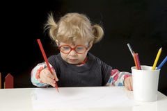 Little blond toddler girl making a drawing. Black background Royalty Free Stock Photos