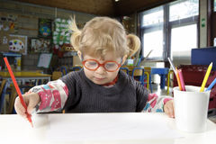 Little blond toddler girl making a drawing. In a classroom Stock Image