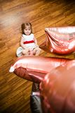Little blonde baby girl two years old with big pink and white balloons lying on the wooden floor on her birthday party royalty free stock images